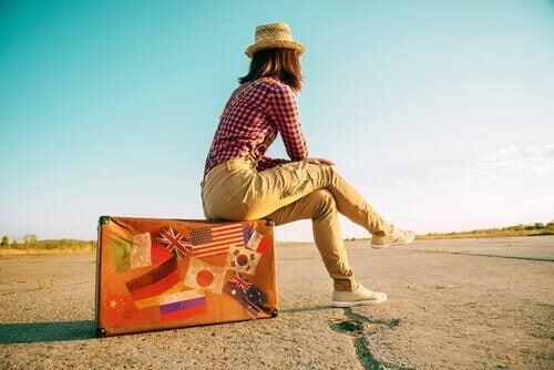 Ragazza seduta su valigia sindrome di wanderlust