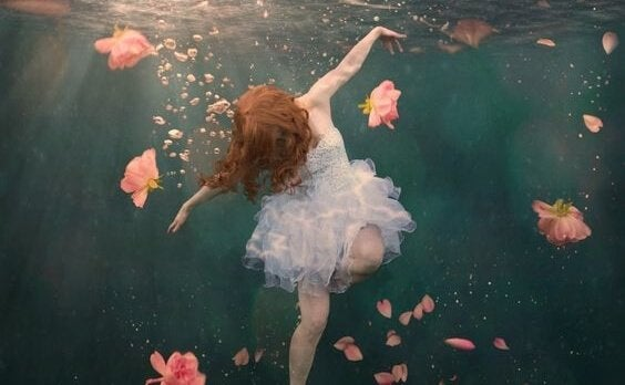 Ragazza sott'acqua circondata da fiori