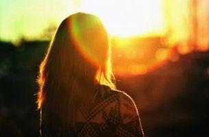 Ragazza di spalle all'alba