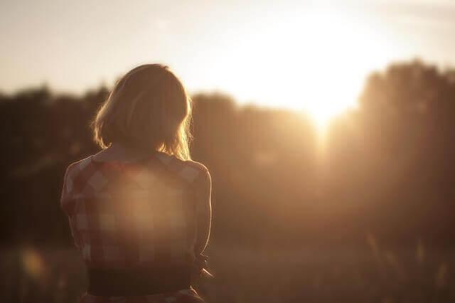 Ragazza triste che guarda il tramonto