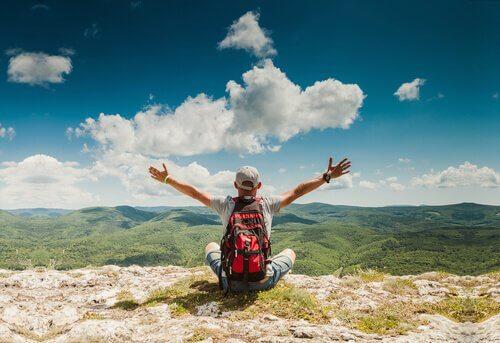 Ragazzo su cima montagna con braccia al cielo