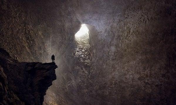 Uomo dentro grotta che guarda via d'uscita