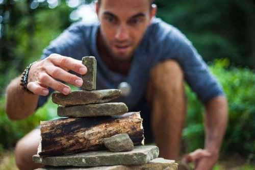 Uomo che costruisce una piramide con dei sassi