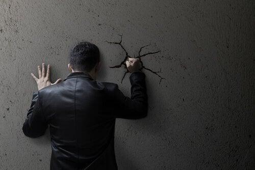 Uomo autodistruttivo che dà un pugno al muro