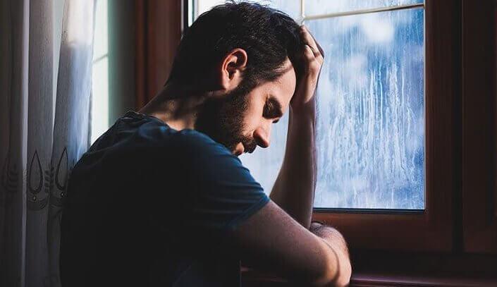 Uomo triste affacciato alla finestra