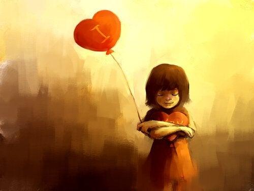 Bambina che abbraccia cuore e ha palloncino a forma di cuore