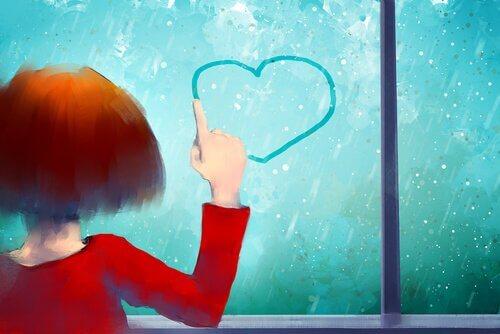 Bambina che col dito disegna cuore su finestra