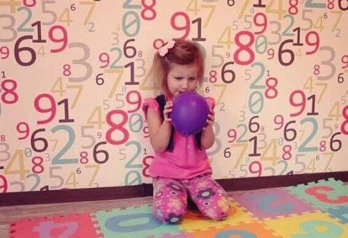 Bambina che gonfia un palloncino per rilassarsi