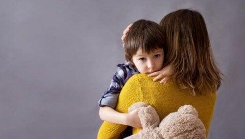 Bambino triste in braccio a sua madre