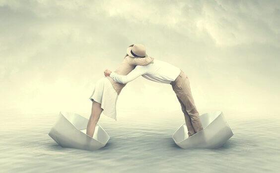 Coppia abbracciata su due diverse barchette di carta