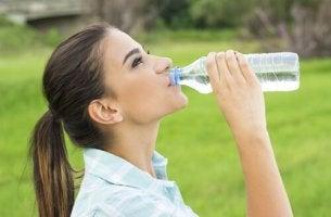 Donna che beve acqua mal di testa da disidratazione