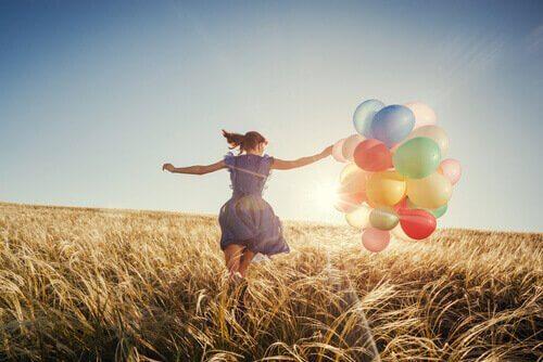 Donna che corre in un campo con dei palloncini