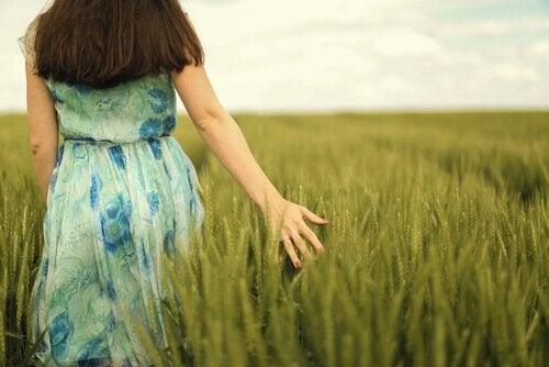 Donna che passeggia in un campo superare il passato