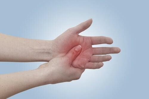 Donna con dolore alla mano per artrite reumatoide