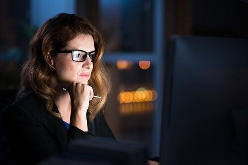 Donna con occhiali e penna che guarda computer di notte