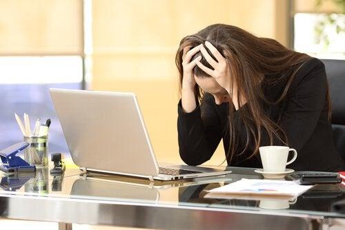 Donna con testa bassa al computer per stress
