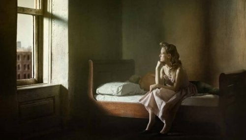 Donna su un letto, davanti a una finestra