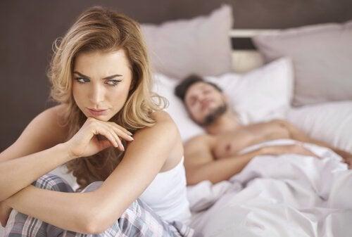 Donna a letto che pensa all'ansia da prestazione