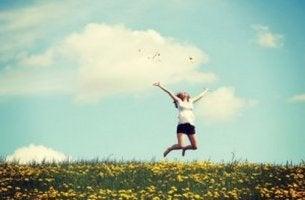 Donna salta felice tra i fiori