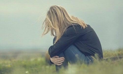 Donna triste seduta sull'erba