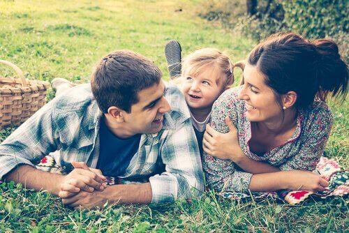 Genitori e figlia stesi sul prato