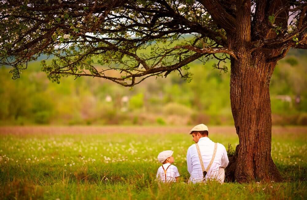 Padre e figlio seduti sotto ad albero