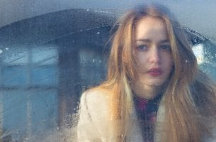 Ragazza bionda triste alla finestra a te, che te ne sei andato