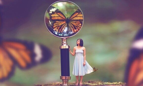 Ragazza con lente con riflesso farfalla