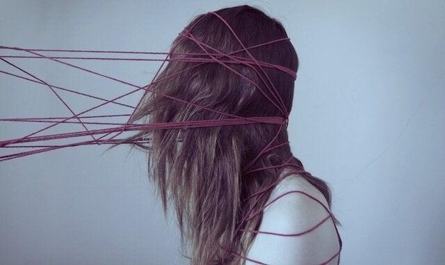 Ragazza con testa intrappolata in fili