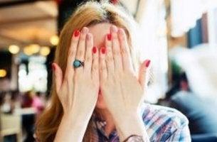 Ragazza che si copre il viso per superare l'imbarazzo