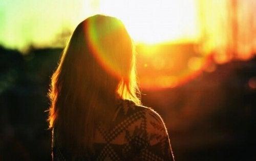 Ragazza di spalle che guarda all'alba
