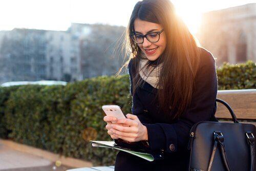 Ragazza seduta sulla panchina con il cellulare