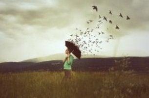 Ragazza con stormo di uccelli affrontare ciò che causa dolore