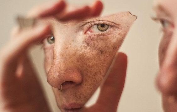 Ragazzo che si guarda in frammento di specchio