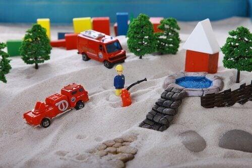 Sabbia con sopra pompieri giocattolo