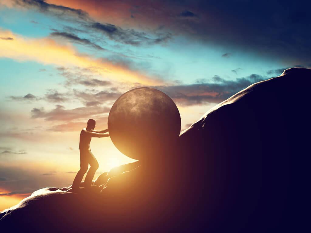 Uomo che trascina masso su montagna a simbolo del superamento personale