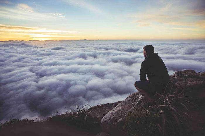 Uomo chinato su montagna che guarda nuvole