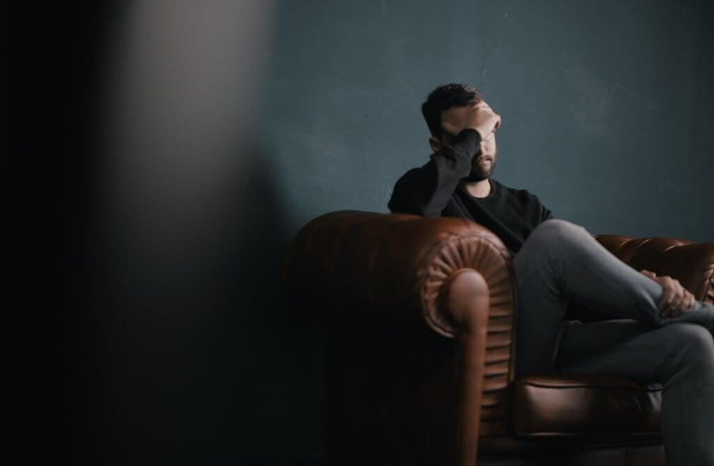 Uomo depresso seduto su poltrona a visita