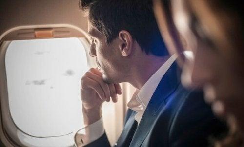 Uomo che guarda dal finestrino di un aereo