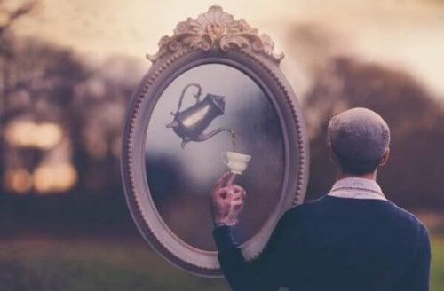 Uomo davanti a uno specchio con una tazza di tè