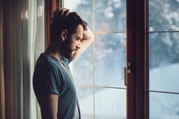 Uomo triste in piedi vicino alla finestra
