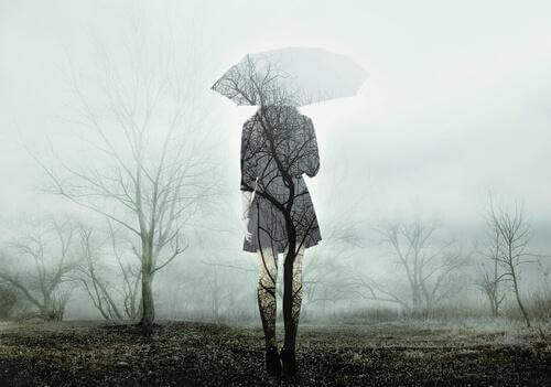 Donna di spalle nebbia e ombrello