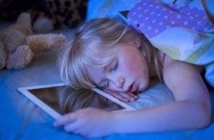 Bambina addormentata su tablet insonnia tecnologica