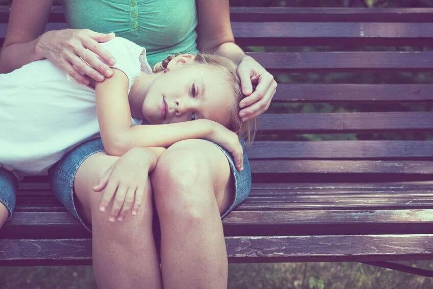 Bambina triste con testa appoggiata su gambe della madre