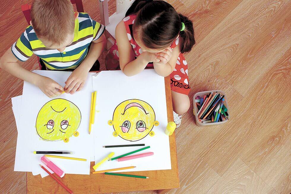 Bambini che disegnano faccine sorridenti e tristi