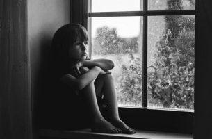 Bambino triste alla finestra