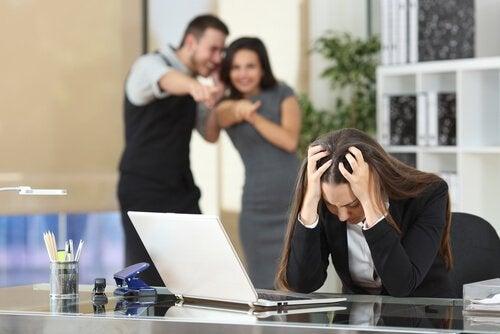 Colleghi di lavoro tossici che deridono un'altra collega