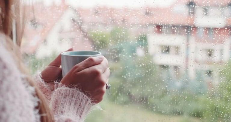 Donna ascolta il rumore della pioggia alla finestra