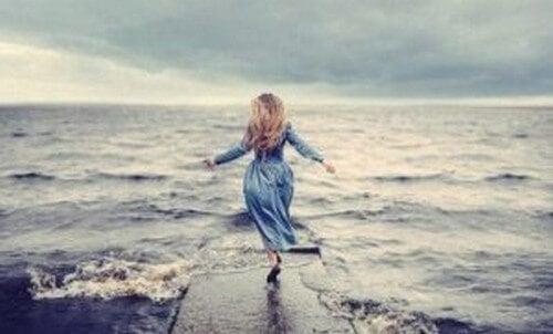 Donna che cammina verso il mare ho bisogno di aiuto