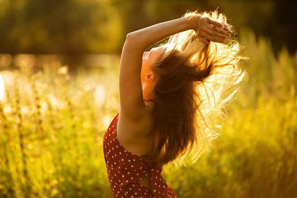 Donna felice in campo che si scuote i capelli